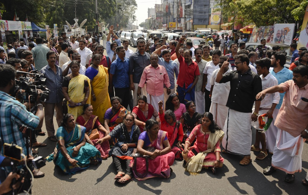 Protestors block traffic and shout slogans reacting to reports of two women of menstruating age entering the Sabarimala temple, one of the world's lar
