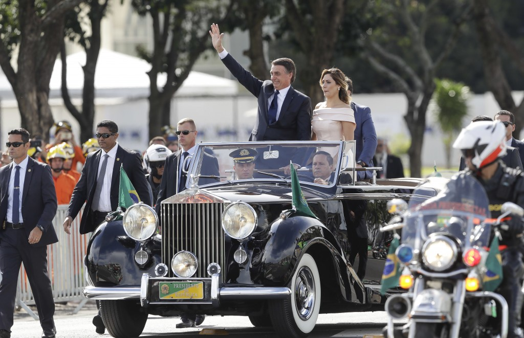 Flanked by first lady Michelle Bolsonaro, Brazil's President Jair Bolsonaro waves as he rides in an open car after his swearing-in ceremony, in Brasil...