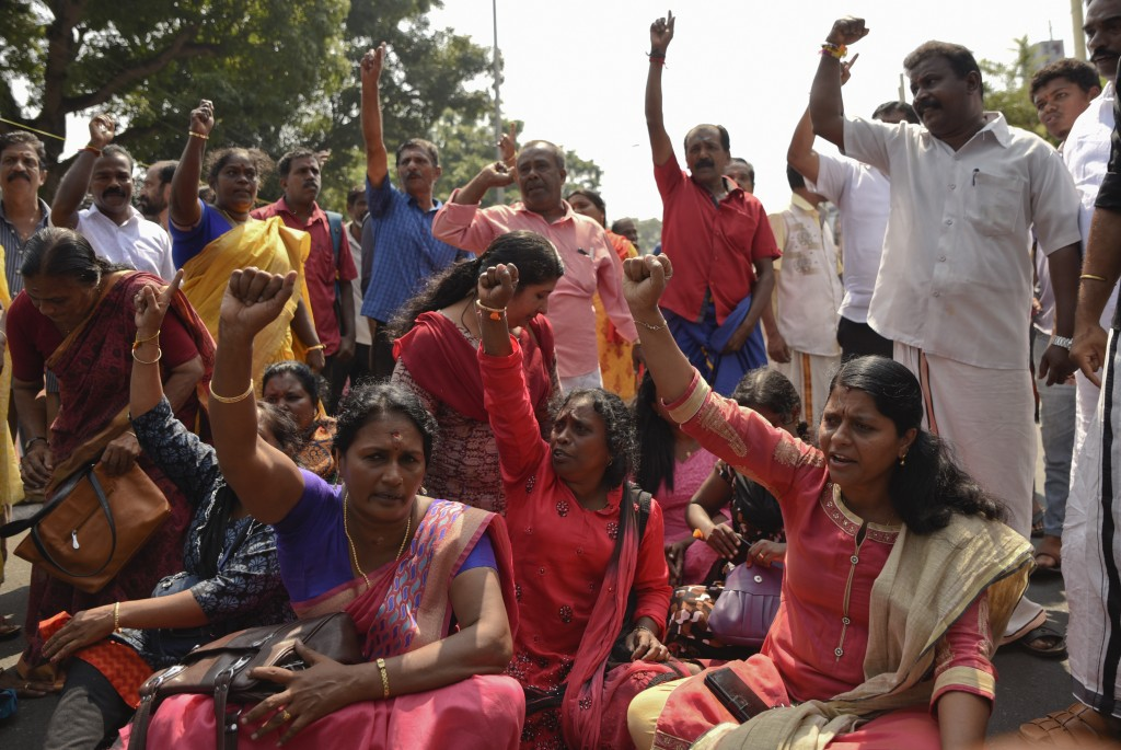 Protestors block traffic and shout slogans reacting to reports of two women of menstruating age entering the Sabarimala temple, one of the world's lar...