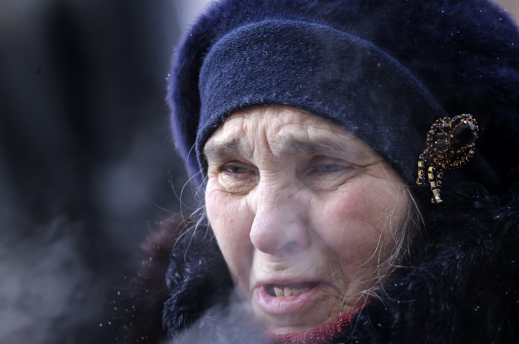 A woman reacts during prayers at the scene of the collapsed apartment building in Magnitogorsk, a city of 400,000 people, about 1,400 kilometers (870 ...