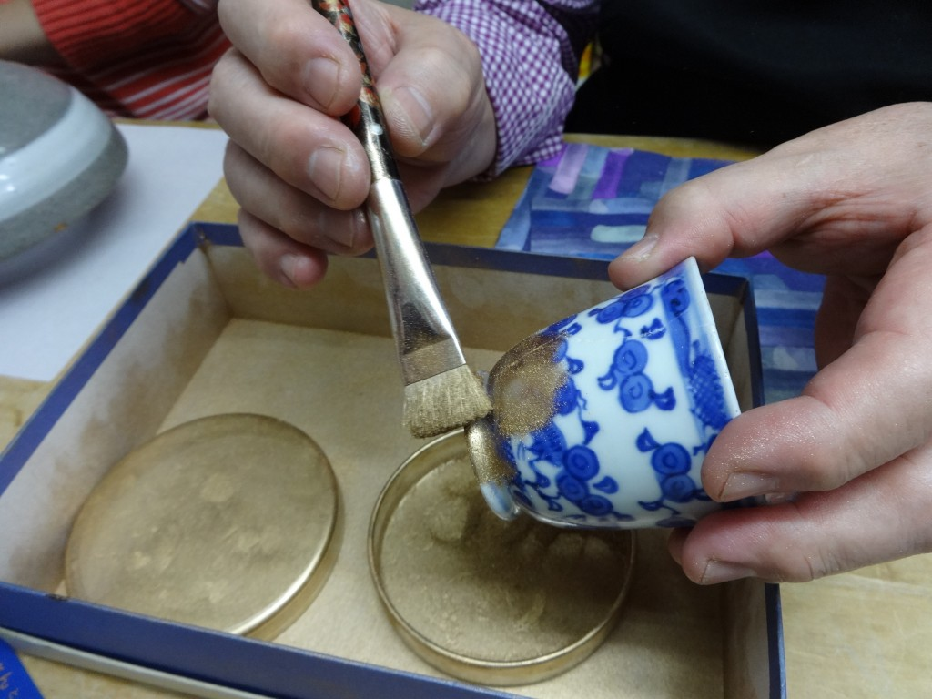 This Nov. 11, 2018 photo shows shows the final step of gold dust being brushed on to the repaired crack at the Kuge Crafts workshop in Tokyo. Kintsugi