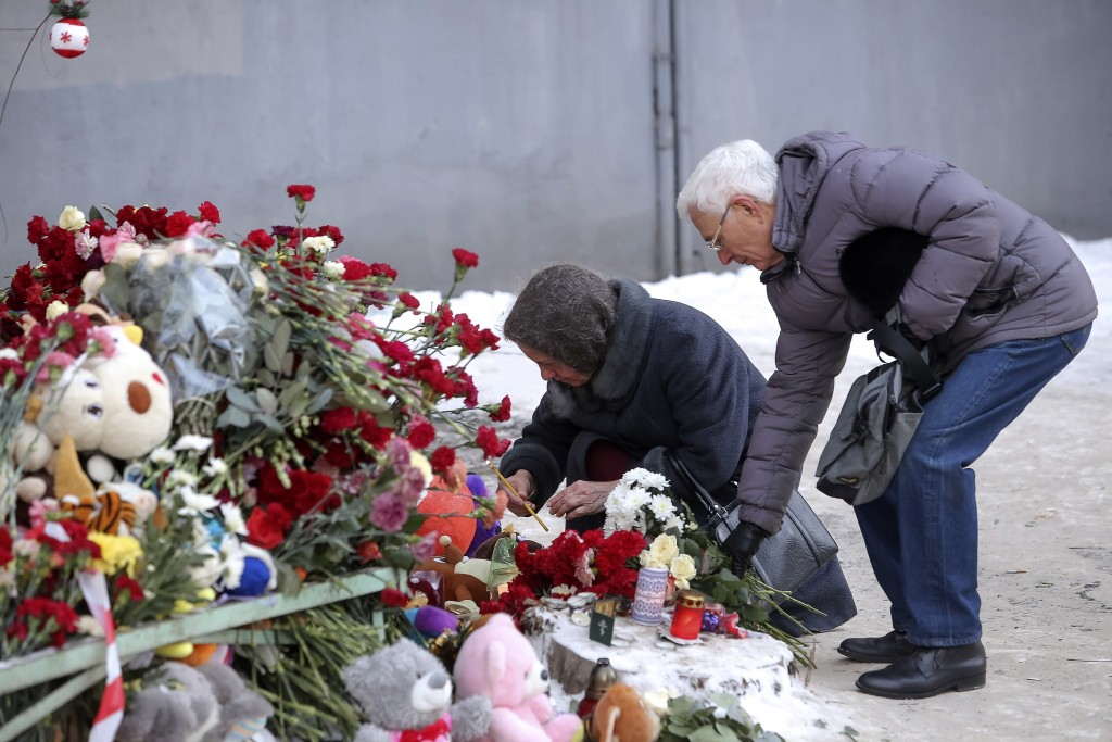 People lay flowers and light candles at the scene of a collapsed apartment building in Magnitogorsk, a city of 400,000 people, about 1,400 kilometers ...