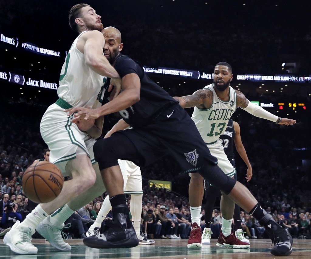 Minnesota Timberwolves forward Taj Gibson, center, collides with Boston Celtics forward Gordon Hayward, left, during the first quarter of an NBA baske