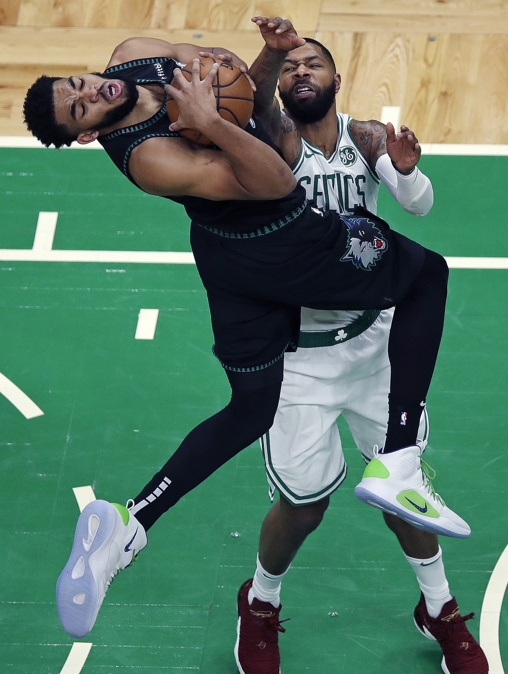 Minnesota Timberwolves center Karl-Anthony Towns, left, is fouled by Boston Celtics forward Marcus Morris on a drive to the basket during the third qu