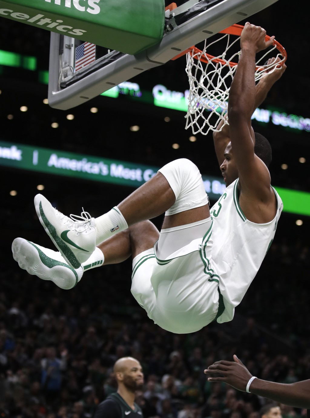 Boston Celtics center Al Horford hangs form the rim after a dunk during the fourth quarter of the team's NBA basketball game against the Minnesota Tim