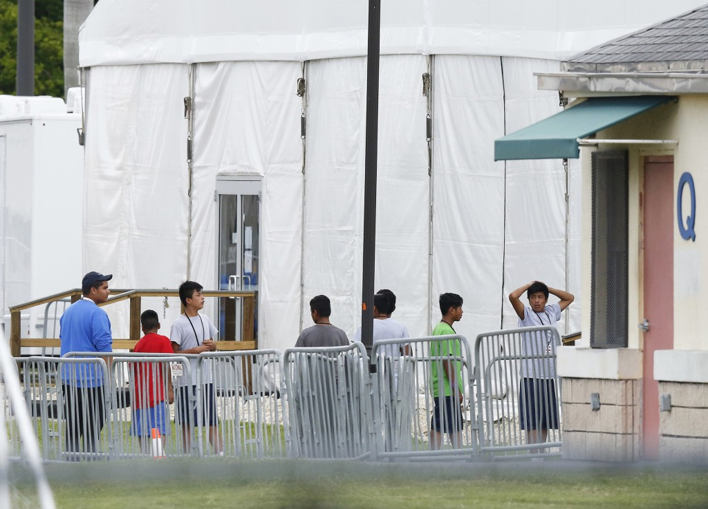FILE - In this June 20, 2018, file photo, immigrant children walk in a line outside the Homestead Temporary Shelter for Unaccompanied Children, a form...