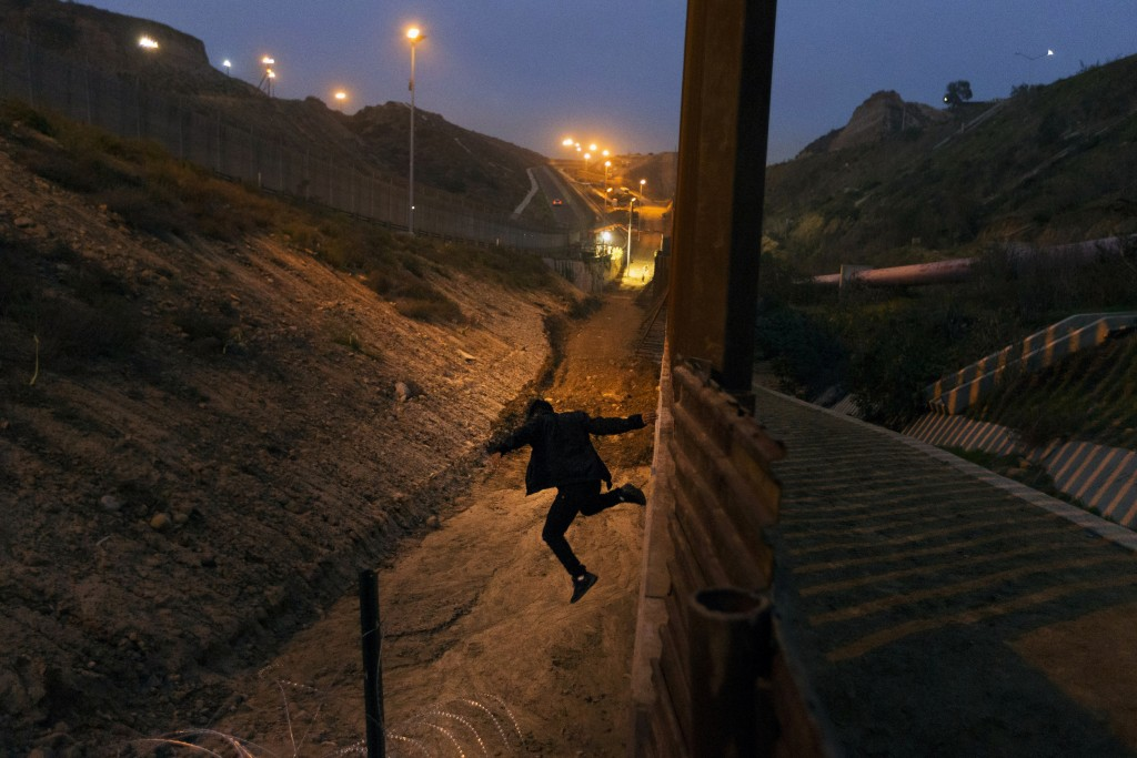 In this Friday, Dec. 21, 2018, file photo, a Honduran youth jumps from the U.S. border fence in Tijuana, Mexico.  Some immigrant youth looking to star...