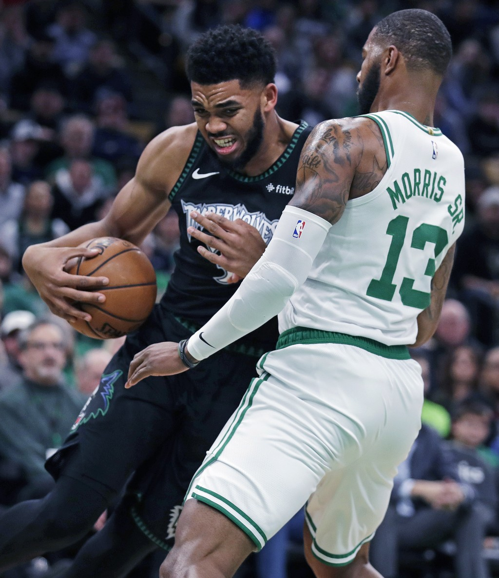 Minnesota Timberwolves center Karl-Anthony Towns, left, grimaces as he collides with Boston Celtics forward Marcus Morris (13) during the first quarte