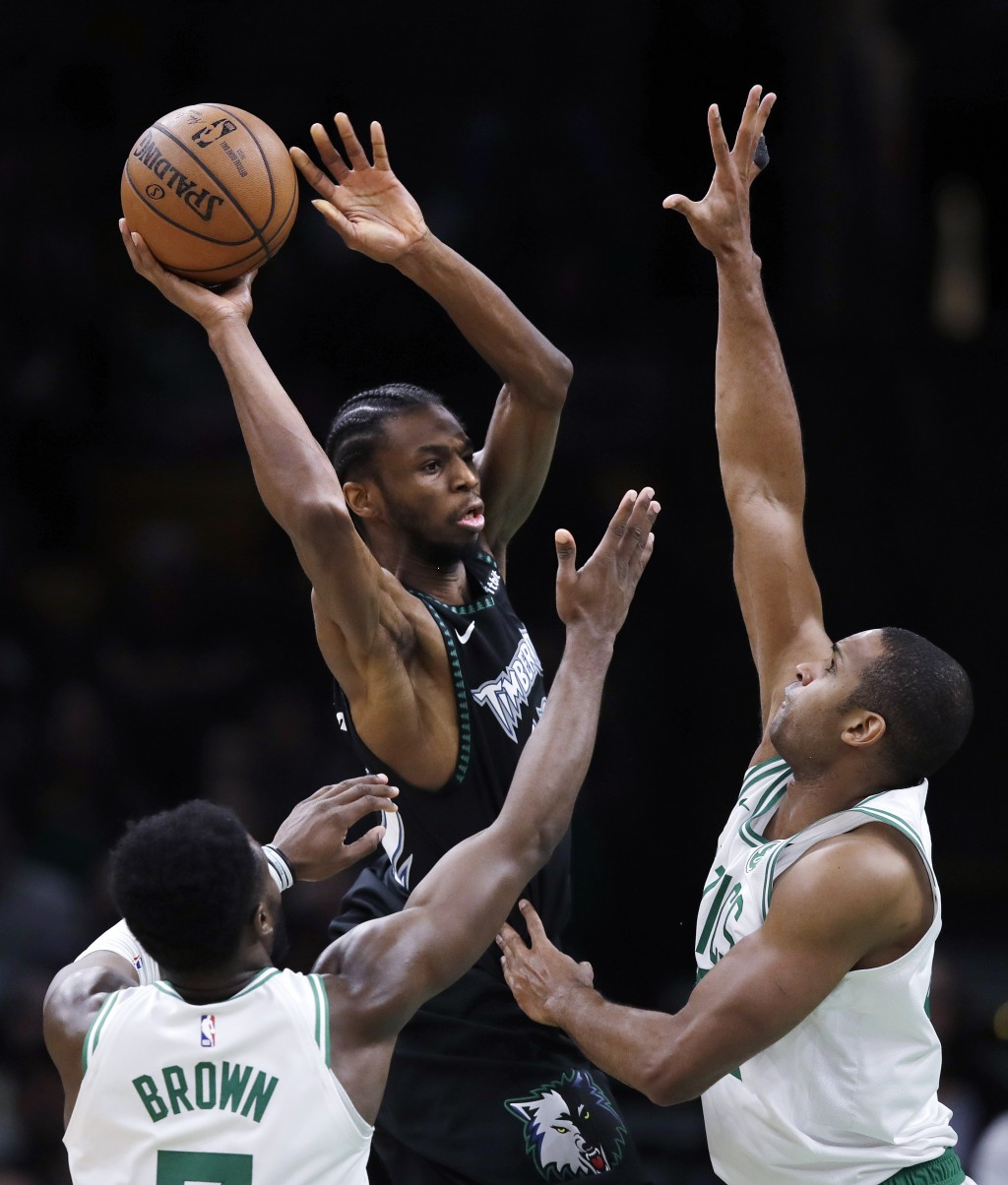 Minnesota Timberwolves forward Andrew Wiggins, center, looks to pass the ball as Boston Celtics center Al Horford, right, and guard Jaylen Brown (7) d