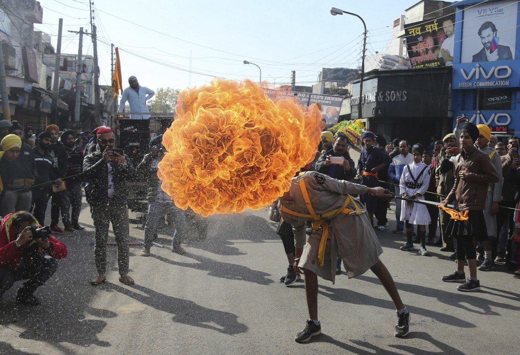 In this Thursday, Jan. 3, 2019, file photo, an Indian Sikh warrior blows fire as he displays traditional martial art skills during a religious process...