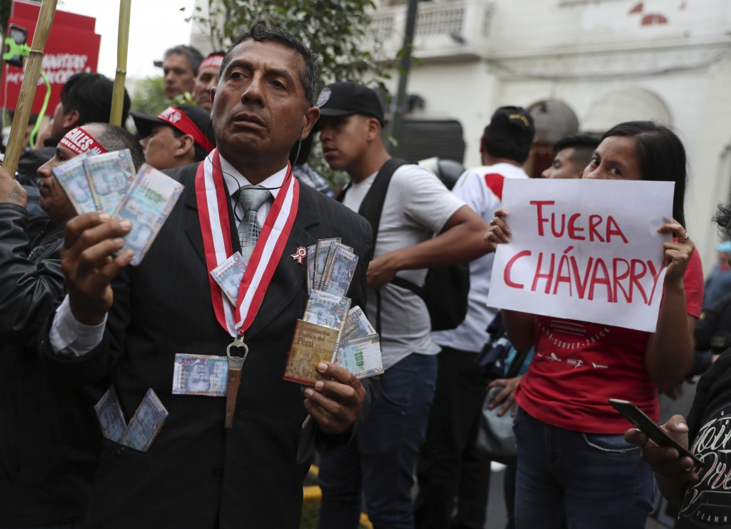 """A protester dressed as a judge shows a miniature copy of Peru's constitution and fake money, next to a woman holding a sign that reads in Spanish """"Cha"""