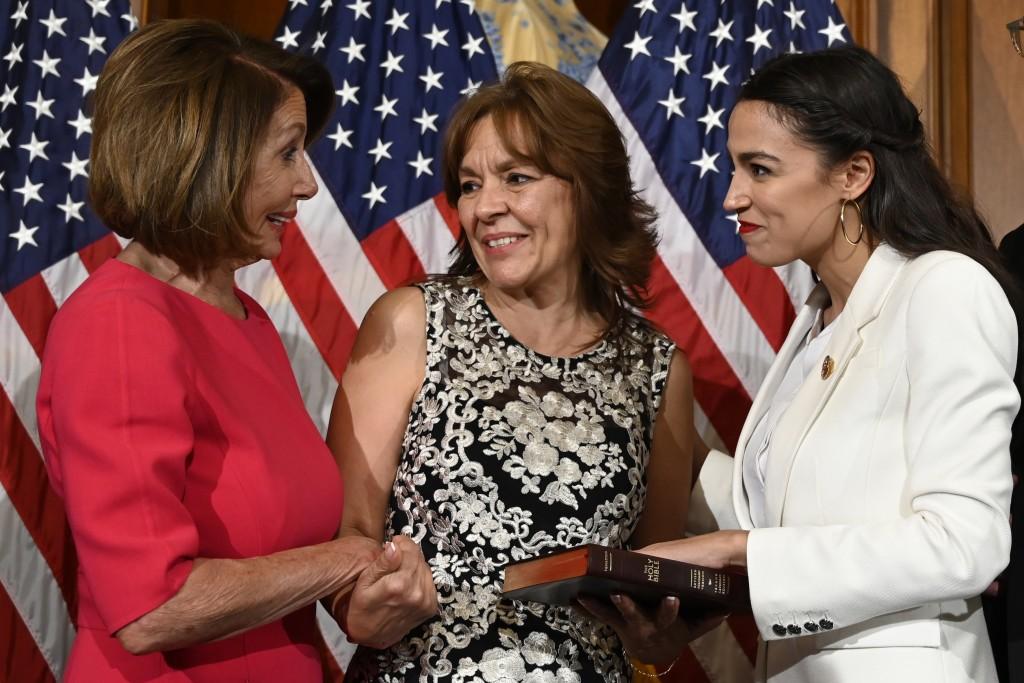 House Speaker Nancy Pelosi of Calif., left, talks with Rep. Alexandria Ocasio-Cortez, D-N.Y., right, and her mother Blanca Ocasio-Cortez, center, duri