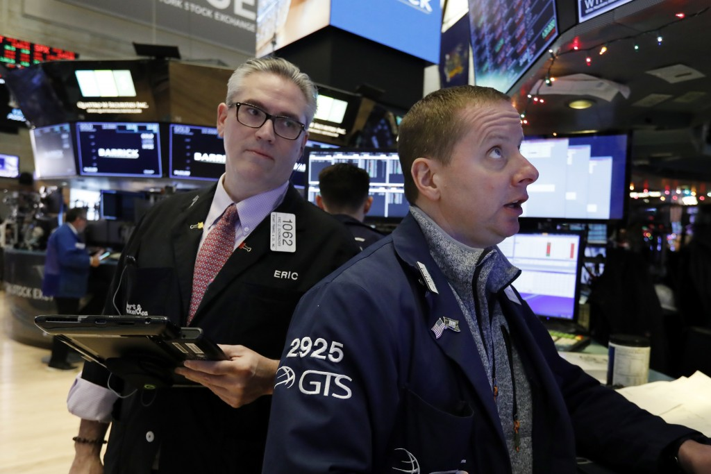 FILE- In this Wednesday, Jan. 2, 2019, photo, trader Eric Schumacher, left, and specialist Robert Nelson work on the floor of the New York Stock Excha...