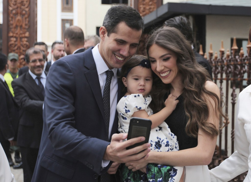 FILE - In this Jan. 5, 2019 file photo, incoming congressional president Juan Guaido, left, takes a selfie photo with his wife Fabiana Rosales and his