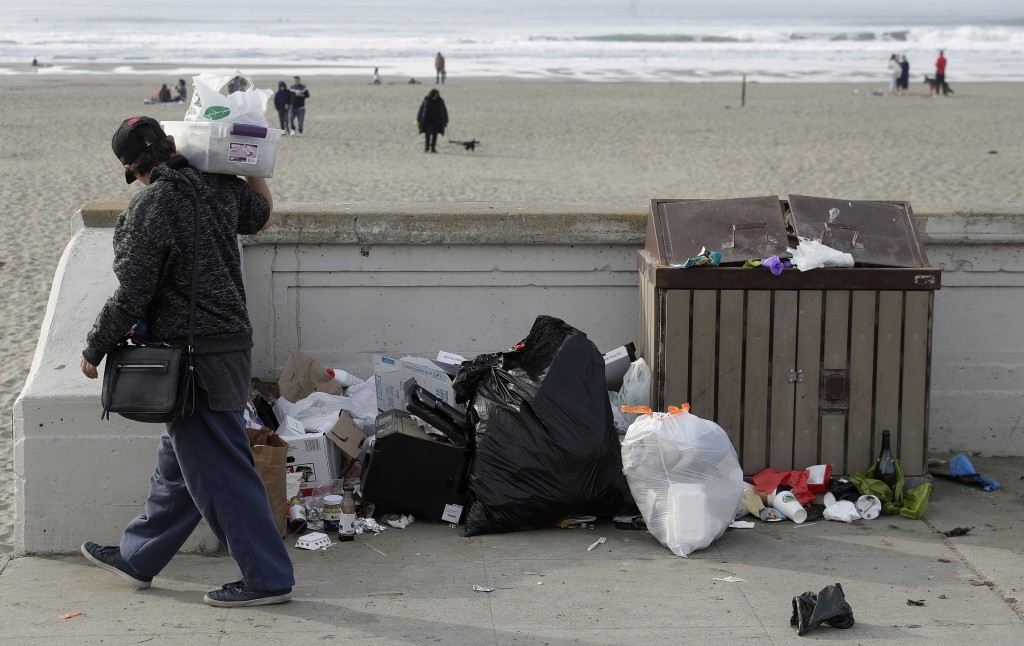 A woman walks past trash piled next to a garbage bin at Ocean Beach in San Francisco, Thursday, Jan. 3, 2019. Nonprofits, businesses and state governm