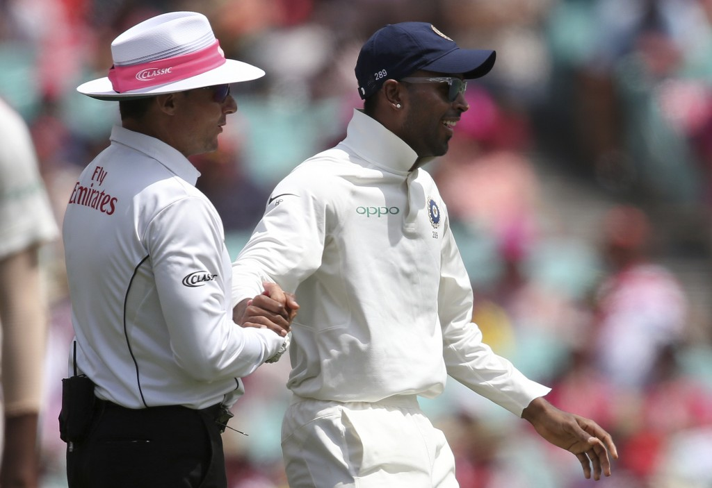India's Hardik Pandya, right, shakes hands with umpire Richard Kettleborough after they collided while Pandya was fielding against Australia on day 3