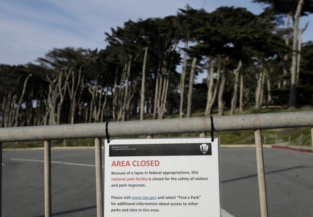 A sign is posted on a gate blocking a parking lot to Land's End in San Francisco, Thursday, Jan. 3, 2019. Nonprofits, businesses and state governments