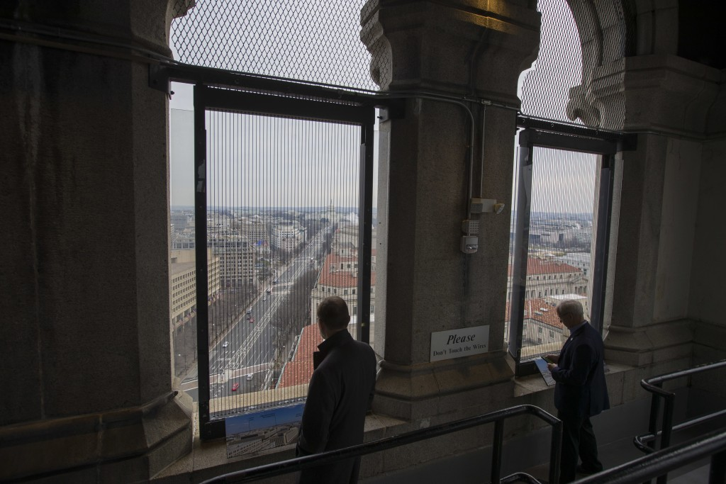 Visitors look out the window of the Old Post Office Pavilion Clock Tower, down Pennsylvania Avenue leading to the U.S. Capitol, Friday, Jan. 4, 2019 i...