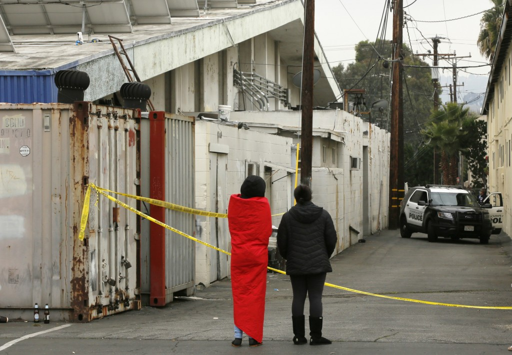 Two unidentified family members await for news from police on their missing family members outside an alley behind the Gable House Bowl in Torrance, C...