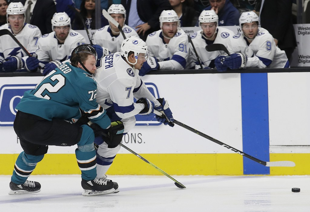 Tampa Bay Lightning right wing Mathieu Joseph (7) reaches for the puck in front of San Jose Sharks defenseman Tim Heed (72), from Sweden, during the s