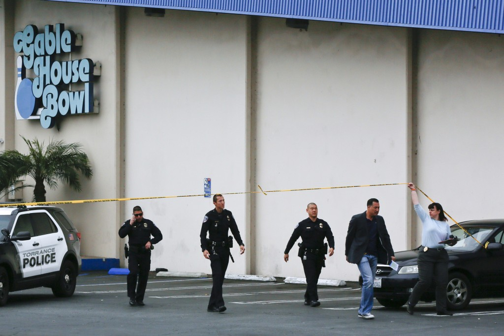 Torrance Police Department investigators walk towards waiting family members, as officers confirm fatalities in a shooting incident at the Gable House