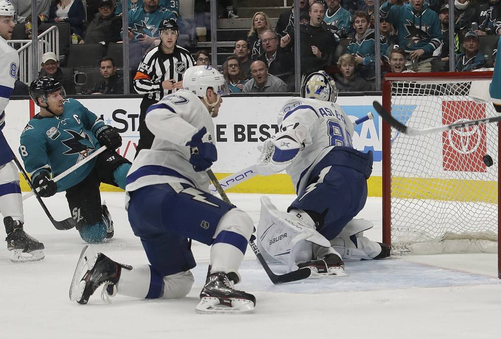 San Jose Sharks center Joe Pavelski, left, scores a goal past Tampa Bay Lightning goaltender Andrei Vasilevskiy, from Russia, right, during the first