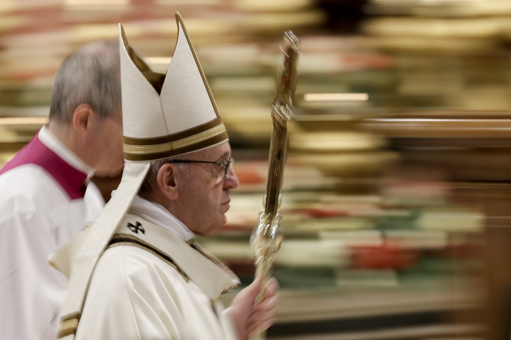 In this photo taken with slow shutter speed Pope Francis leaves after celebrating an Epiphany Mass in St. Peter's Basilica at the Vatican, Sunday, Jan
