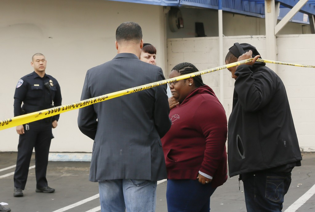 Torrance Police Department investigators, left, confirm fatalities to waiting family members, right, after a shooting incident at the Gable House Bowl...