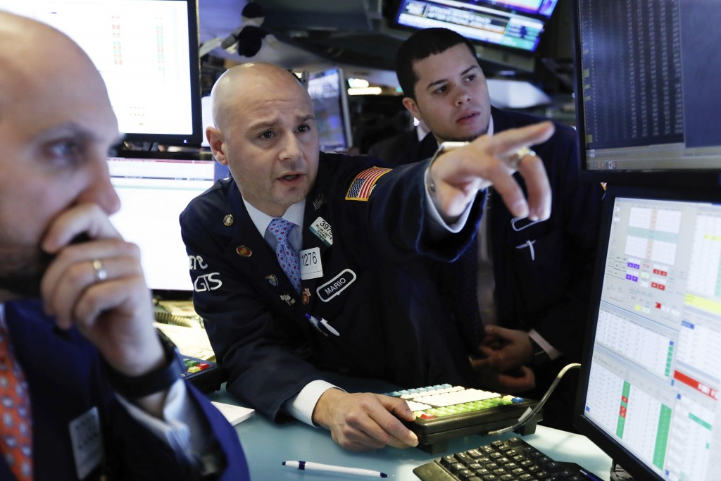 FILE- In this Jan. 4, 2019, file photo Mario Picone, center, works with fellow specialists on the floor of the New York Stock Exchange. The U.S. stock...