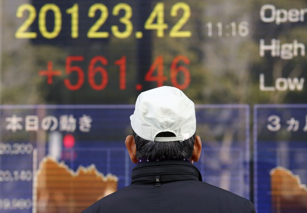 A man looks at an electronic stock board of a securities firm in Tokyo, Monday, Jan. 7, 2019. Asian markets were broadly higher on Monday after strong...