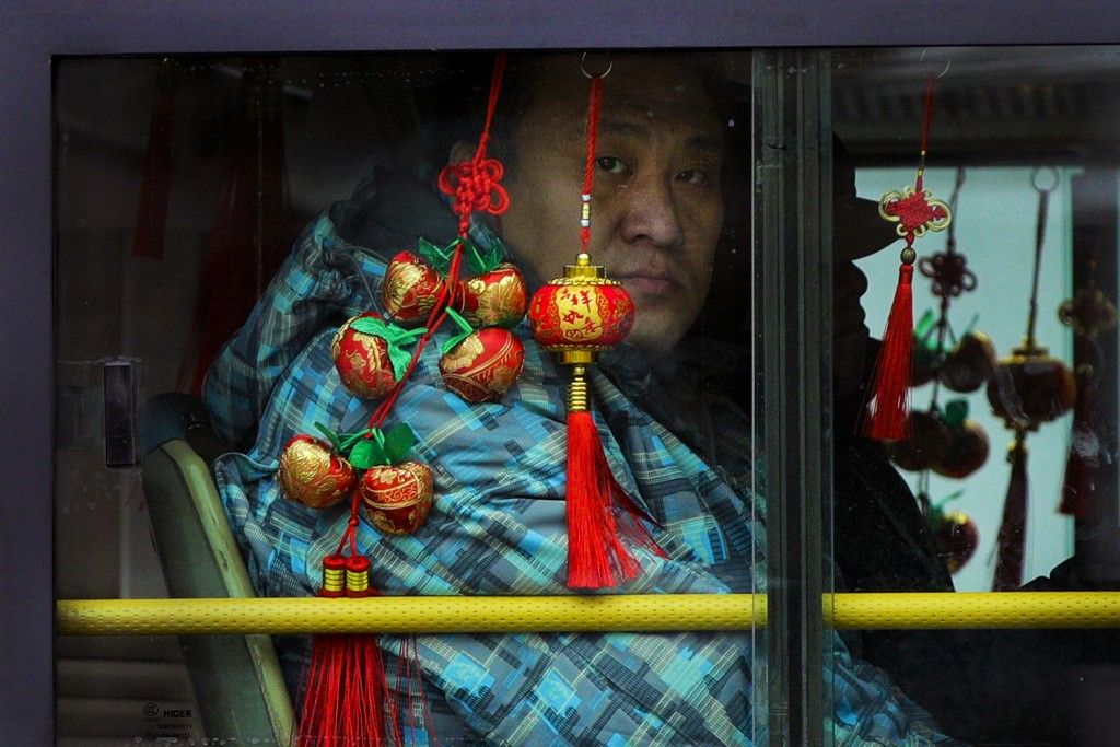 FILE - In this Monday, Jan. 7, 2019, file photo, a commuter looks out from a bus window decorated with Chinese New Year decoration traveling on a road