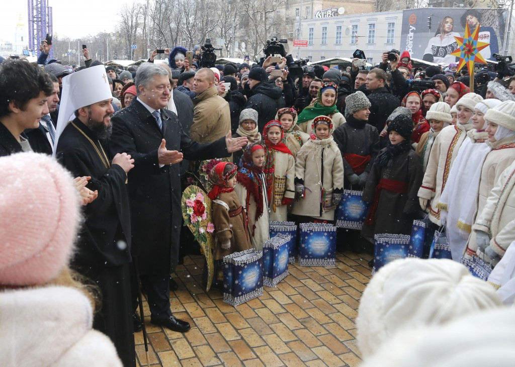 Metropolitan Epiphanius, the head of the independent Ukrainian Orthodox Church, second left, and Ukrainian President Petro Poroshenko react with belie...
