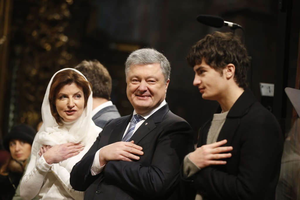 Ukrainian President Petro Poroshenko, center, his wife Maryna, left, and his son, right, attend the service marking Orthodox Christmas and celebrating...