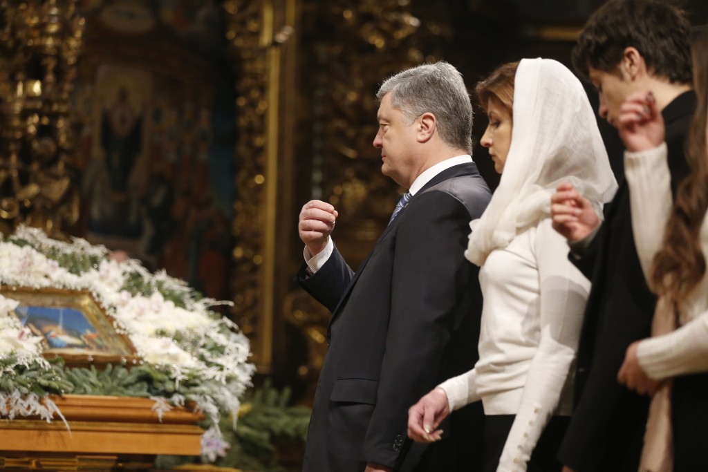 Ukrainian President Petro Poroshenko, third right, his wife Maryna, second right, and his son cross themselves during the service marking Orthodox Chr...