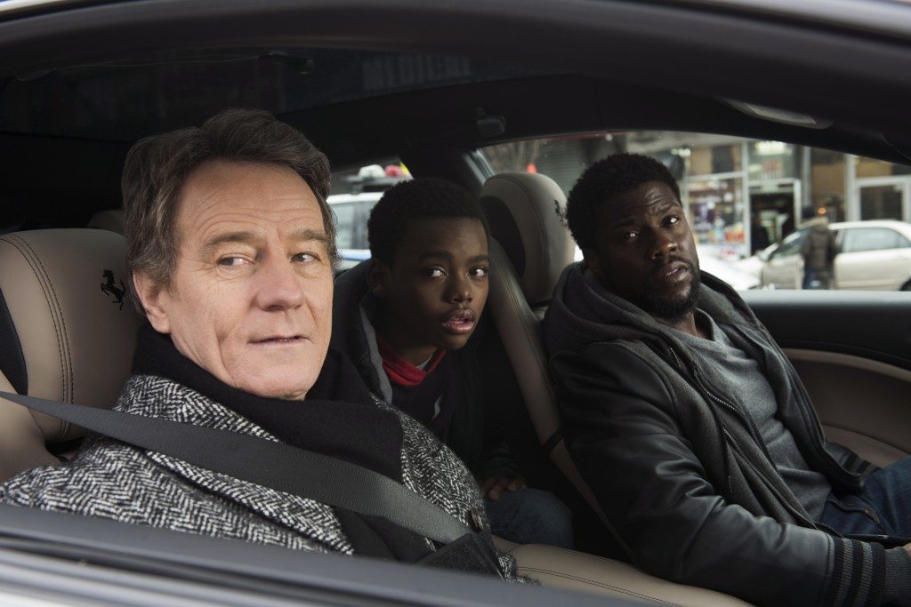 """This image released by STXfilms shows Bryan Cranston, from left, Jahi Di'Allo Winston, and Kevin Hart in a scene from """"The Upside."""" (David Lee/STXfilm..."""