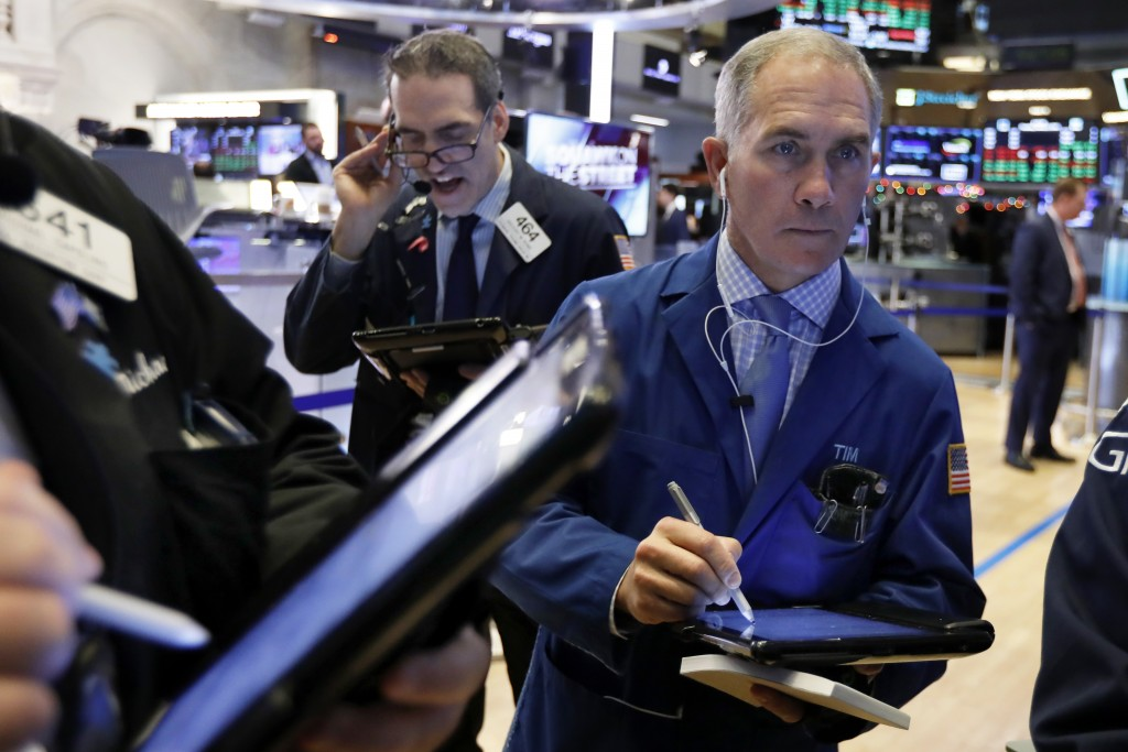 FILE- In this Jan. 3, 2019, file photo Timothy Nick, right, works with fellow traders on the floor of the New York Stock Exchange. The U.S. stock mark...