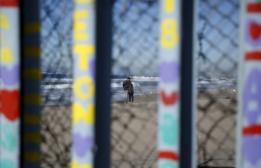 Two people embrace on the U.S. side of the border, seen through the border wall Monday, Jan. 7, 2019, seen from along the beach in Tijuana, Mexico. U.