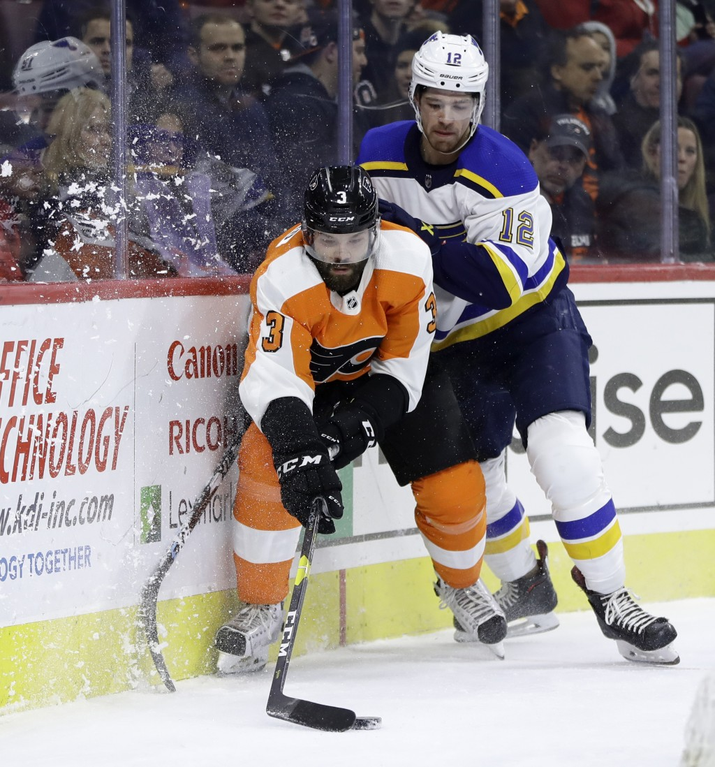 Philadelphia Flyers' Radko Gudas (3) tries to keep the puck away from St. Louis Blues' Zach Sanford (12) during the first period of an NHL hockey game...