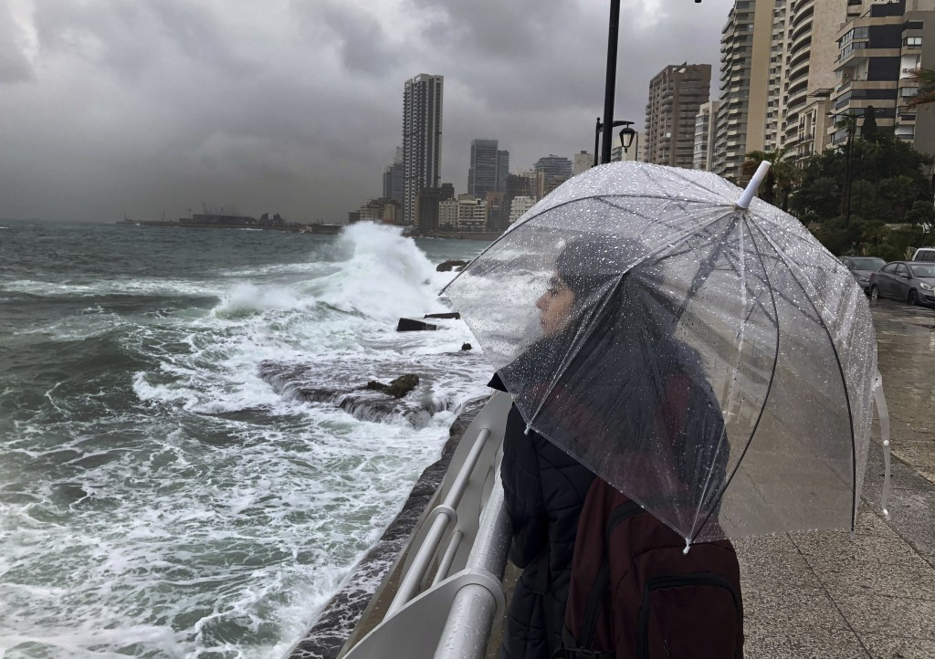 A Lebanese girl shelters for the rain, as she watches waves crash into the seawall on the Mediterranean Sea, in Beirut, Lebanon, Tuesday, Jan. 8, 2019...