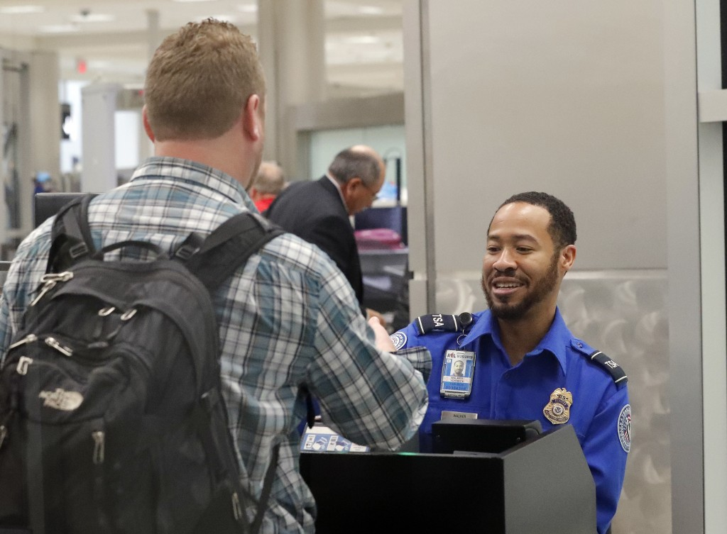 A Transportation Security Administration employee helps air travelers check in at a TSA security checkpoint at Hartsfield Jackson Atlanta Internationa