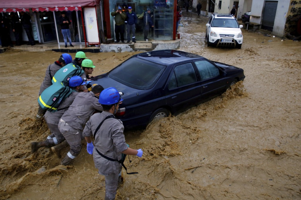 Civil Defense workers struggle to push a stranded car on a street in Beirut, Lebanon, Tuesday, Jan. 8, 2019. A strong storm and heavy rainfall turned ...