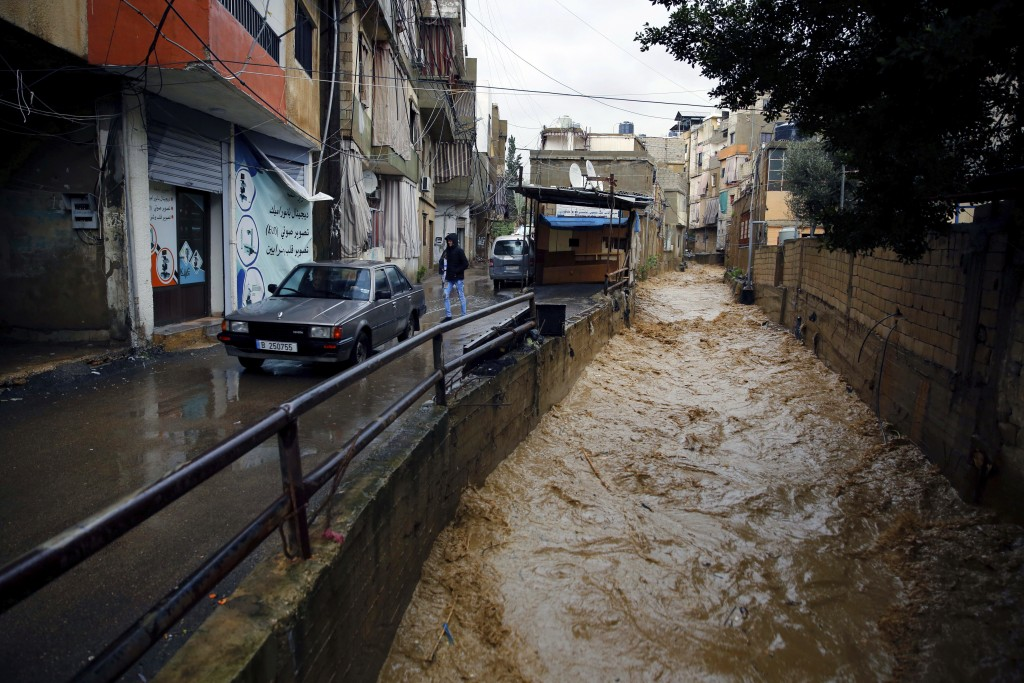 People walk next to a canal that flows from rainwater in Beirut, Lebanon, Tuesday, Jan. 8, 2019. A strong storm and heavy rainfall turned streets in L