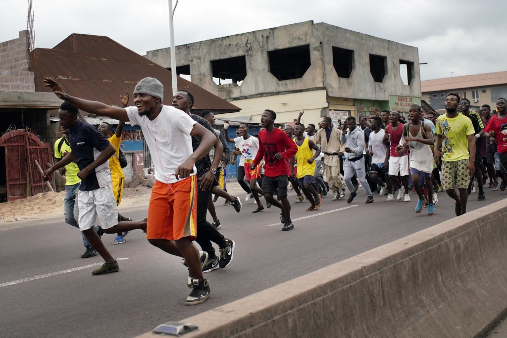 Congolese sportsmen run towards the main stadium in Kinshasa, Congo, Tuesday Jan. 8, 2019, to participate in a general boxing and martial arts competi...