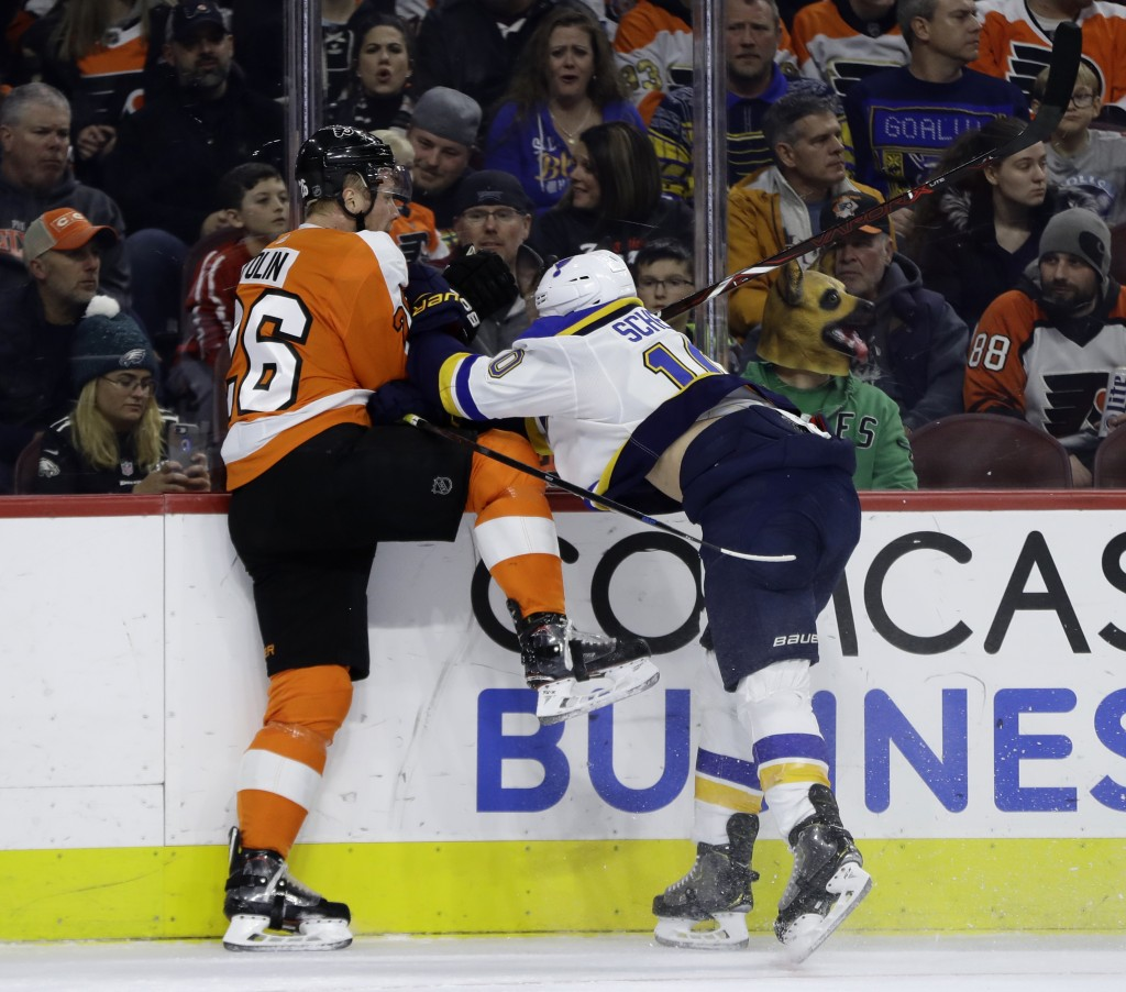 St. Louis Blues' Brayden Schenn, right, checks Philadelphia Flyers' Christian Folin into the boards during the first period of an NHL hockey game, Mon...