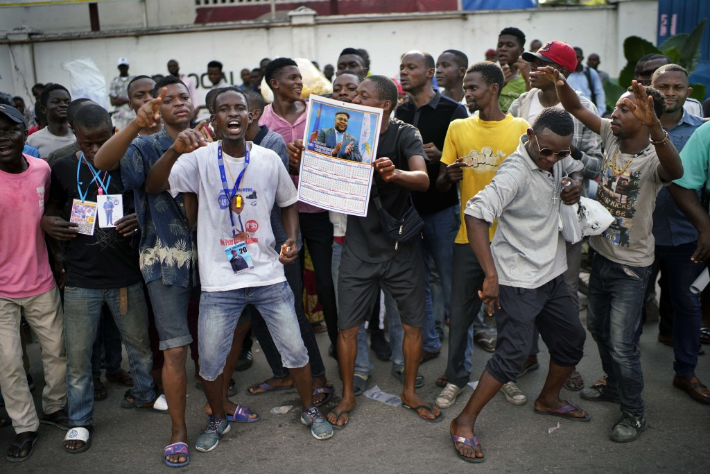 Congolese supporters of opposition Presidential candidate Felix Tshisekedi stand outside the UDPS party headquarters in Kinshasa, Congo, Monday Jan. 7
