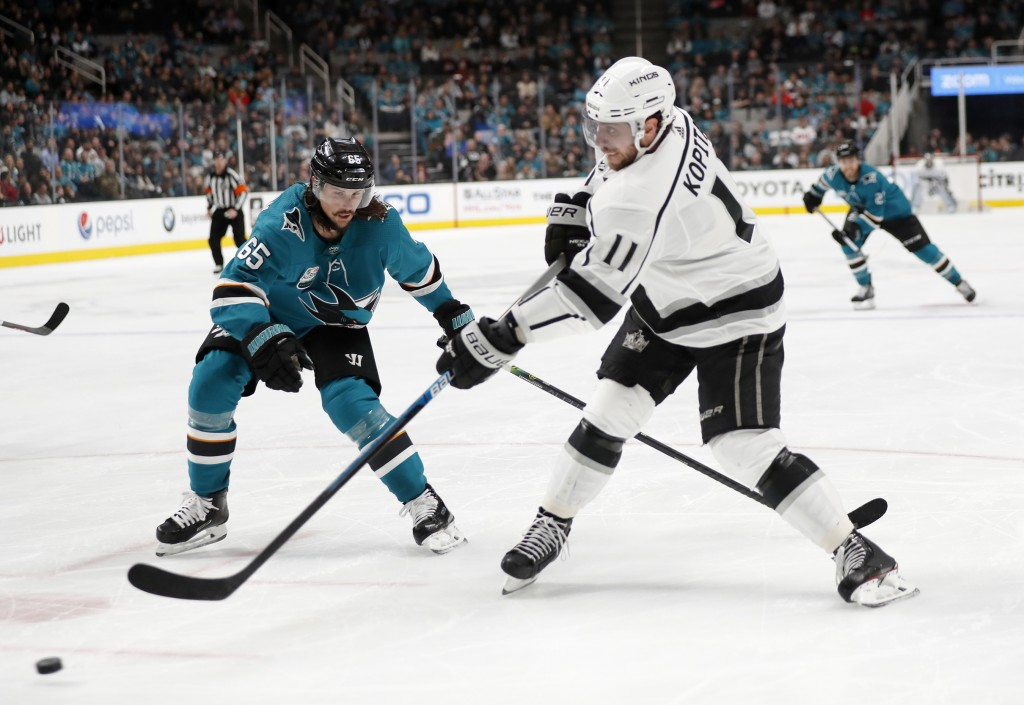 Los Angeles Kings' Anze Kopitar (11) fires the puck at the net against San Jose Sharks' Erik Karlsson (65) in the second period of an NHL hockey game