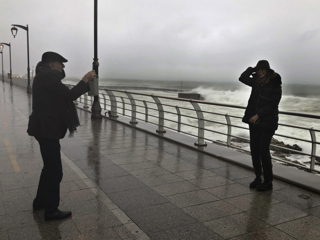 Walid Jumblatt, left, the political leader of Lebanon's minority Druse sect, takes pictures of his wife Nura, as waves break, on the Mediterranean wat