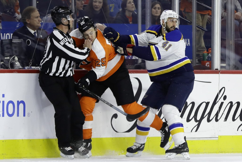 Philadelphia Flyers' James van Riemsdyk, center, is shoved into an official by St. Louis Blues' Robert Bortuzzo, right, during the first period of an ...