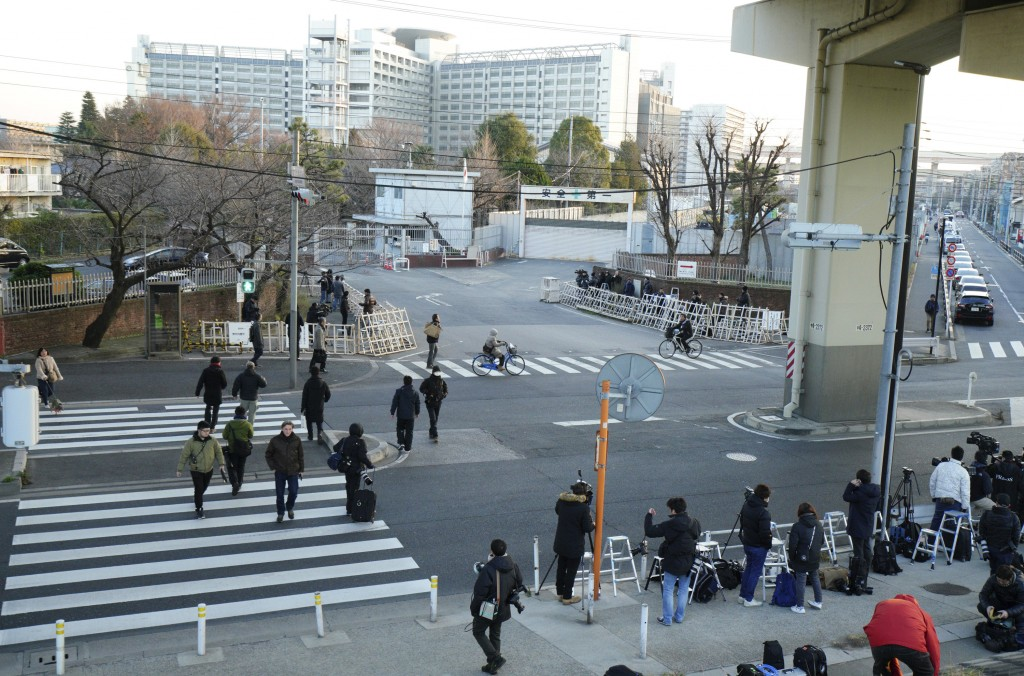 Tokyo Detention Center is seen as journalists wait for a vehicle presumably carrying former Nissan chairman Carlos Ghosn leaves the center in Tokyo on...
