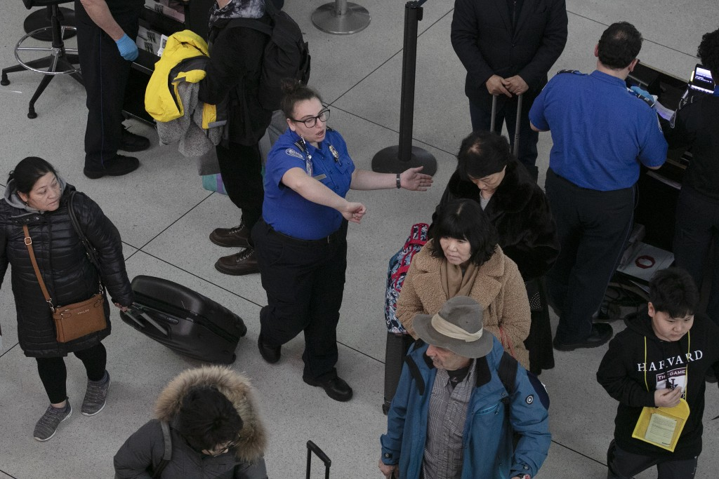A TSA agent, center, directs passengers through a security checkpoint, Monday, Jan. 7, 2019, at New York's John F. Kennedy International Airport. Sena...